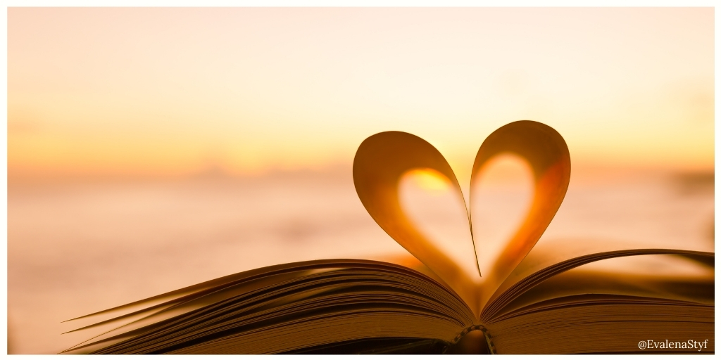 A book on the beach at dawn. Some of the pages have been folded into a heart.