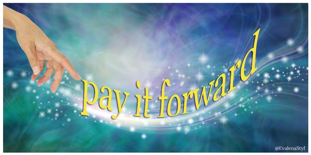 A hand points to the glittering text that reads: Pay it forward