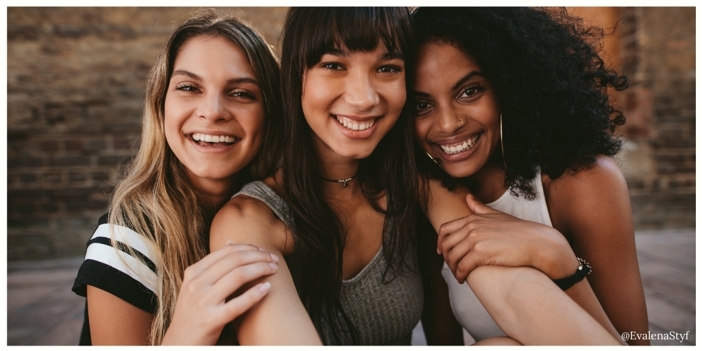 Three women are standing close together and smiling at the camera
