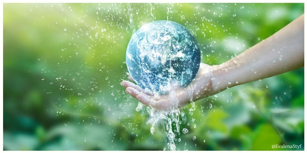 Be kind to the environment: A hand gently holds our planet under running water in front of a field of green
